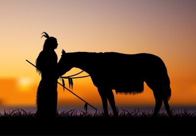 A Native American with a horse at sunset